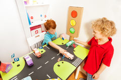 Happy friends playing drivers with their toy cars royalty free stock photo
