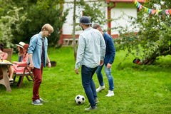 Happy friends playing football at summer garden Royalty Free Stock Images