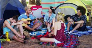 Friends playing guitar and having drinks at music festival 4k. Happy friends playing guitar and having drinks at music festival 4k stock video