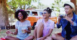 Friends playing guitar and having drinks at music festival 4k. Happy friends playing guitar and having drinks at music festival 4k stock footage