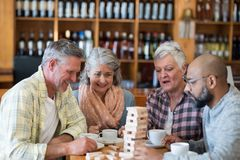 Happy friends playing jenga game while having cup of coffee. In bar Stock Photo