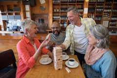 Happy friends playing jenga game while having cup of coffee. In bar Royalty Free Stock Photo
