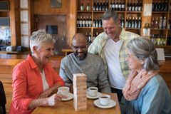 Happy friends playing jenga game while having cup of coffee. In bar Royalty Free Stock Photography