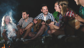 Happy friends playing music and enjoying bonfire Stock Image