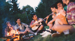 Happy friends playing music and enjoying bonfire Stock Photos