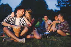 Happy friends playing music and enjoying bonfire Stock Photo