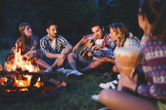 Happy friends playing music and enjoying bonfire. In nature Stock Images