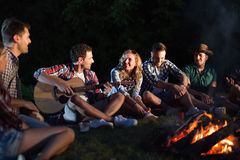 Happy friends playing music and enjoying bonfire Royalty Free Stock Photos