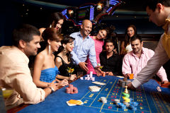 Happy friends playing roulette in a casino Royalty Free Stock Photography