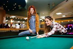 Two female friends playing snooker. Happy friends playing snooker and billiards at club Stock Photography