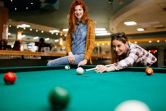 Two female friends playing snooker. Happy friends playing snooker and billiards at club Royalty Free Stock Image