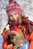 Happy friends playing with snow. White girl having fun with baby animal in winter season Royalty Free Stock Photos