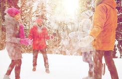 Happy friends playing with snow in winter forest Royalty Free Stock Photos