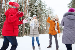 Happy friends playing snowball in winter forest Royalty Free Stock Photo