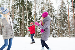 Happy friends playing snowball in winter forest Stock Images