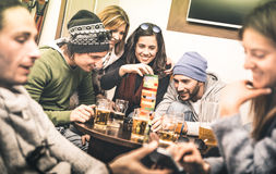 Happy friends playing table board game while drinking beer. At pub - Cheerful people having fun at brewery bar corner royalty free stock image