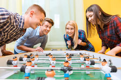 Happy friends playing table hockey Royalty Free Stock Image