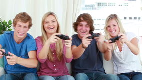 Happy friends playing video games together Stock Image