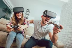 Happy friends playing video games with virtual reality glasses. Young people having fun with new technology console online Royalty Free Stock Image
