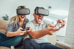 Happy friends playing video games with virtual reality glasses. Young people having fun with new technology console online Stock Photos