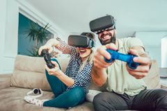 Happy friends playing video games with virtual reality glasses. Young people having fun with new technology console online Stock Photo