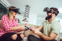 Happy friends playing video games with virtual reality glasses. Young people having fun with new technology console online Royalty Free Stock Images
