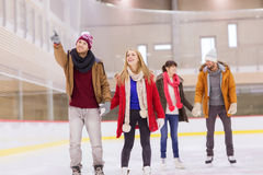 Happy friends pointing finger on skating rink Royalty Free Stock Image