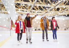 Happy friends pointing finger on skating rink Royalty Free Stock Photography