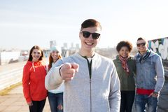 Happy friends pointing finger to you on street Stock Images