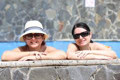 Happy friends in the pool. Focus in the right lady Stock Photos