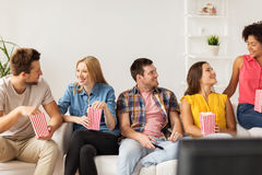 Happy friends with popcorn and tv remote at home Royalty Free Stock Images