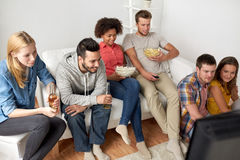 Happy friends with popcorn watching tv at home Stock Photos