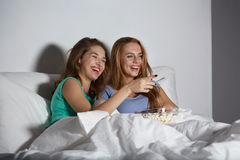 Happy friends with popcorn and watching tv at home Stock Photography