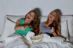Happy friends with popcorn and watching tv at home. Friendship, people, pajama party, entertainment and junk food concept - happy friends or teenage girls eating Royalty Free Stock Image