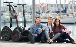 Happy friends posing near segways on shore Royalty Free Stock Photos