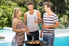 Happy friends preparing barbecue near pool Stock Photo