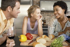 Happy Friends With Preparing Food At Kitchen Counter. Smiling multiethnic friends with preparing food at kitchen counter stock images