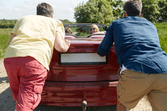 Happy friends pushing broken cabriolet car Royalty Free Stock Photos