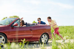 Happy friends pushing broken cabriolet car Stock Photography