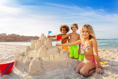 Free Happy Friends Putting Flags Into Sandcastle Towers Royalty Free Stock Photo - 131412705