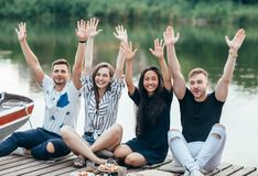 Happy friends raised hands relaxing on picnic outdoors on river. Vacation, fun and success concept stock images