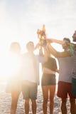 Happy friends raising beer bottles. On the beach Stock Photos