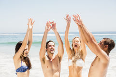 Happy friends raising their hands on the beach Royalty Free Stock Image