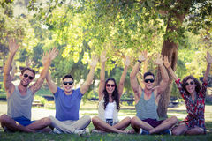 Happy friends raising their hands in the park Royalty Free Stock Image