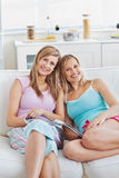 Happy friends reading a magazine at home Royalty Free Stock Photography