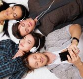 Happy friends relaxing with gadgets. Happy multiracial friends relaxing on a carpet with gadgets Stock Photography