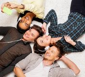 Happy friends relaxing with gadgets. Happy multiracial friends relaxing on a carpet with gadgets Royalty Free Stock Photo