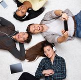 Happy friends relaxing with gadgets Royalty Free Stock Images