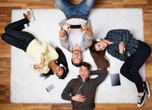 Happy friends relaxing with gadgets. Happy multiracial friends relaxing on a carpet with gadgets Stock Images