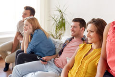 Happy friends with remote watching tv at home Stock Images
